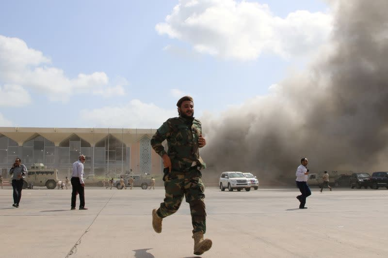 FILE PHOTO: Security personnel and people react during an attack on Aden airport moments after a plane landed carrying a newly formed cabinet for government-held parts of Yemen, in Aden