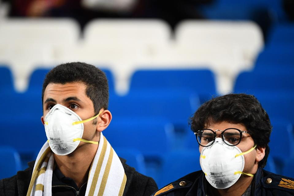 Football fans wearing masks in light of the coronavirus outbreak wait for the start of the Spanish League football match between Real Madrid and Barcelona at the Santiago Bernabeu stadium in Madrid on March 1, 2020. (Photo by GABRIEL BOUYS / AFP) (Photo by GABRIEL BOUYS/AFP via Getty Images)