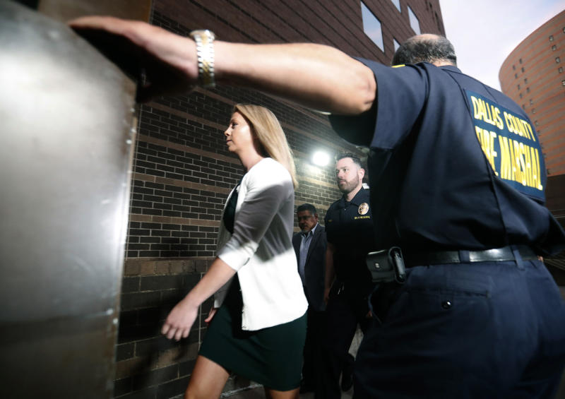 In this Tuesday, Sept. 24, 2019, Amber Guyger, center, walks flanked by security while arriving for her murder trial at the Frank Crowley Courthouse in downtown Dallas. Security has been ramped up around the white former Dallas police officer's high-profile trial for murder in the killing of her unarmed black neighbor. The Dallas Police Association says threats have forced the group to hire private security for Guyger and her lawyers.  (AP Photo/LM Otero)