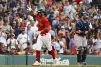 Boston Red Sox's Jonathan Arauz, left, points toward the stands as he crosses home past Tampa Bay Rays catcher Francisco Mejia after his home run during the seventh inning of a baseball game Monday, Sept. 6, 2021, at Fenway Park in Boston. (AP Photo/Winslow Townson)