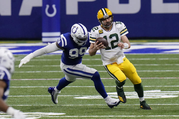 Green Bay Packers quarterback Aaron Rodgers (12) runs from Indianapolis Colts' DeForest Buckner (99) during the first half of an NFL football game, Sunday, Nov. 22, 2020, in Indianapolis. (AP Photo/AJ Mast)