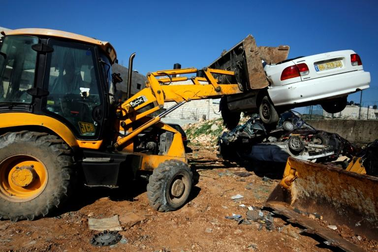 A bulldozer smashes a car as part of efforts to combat an underground market for vehicles stolen in Israel or deemed not roadworthy transported into the occupied West Bank