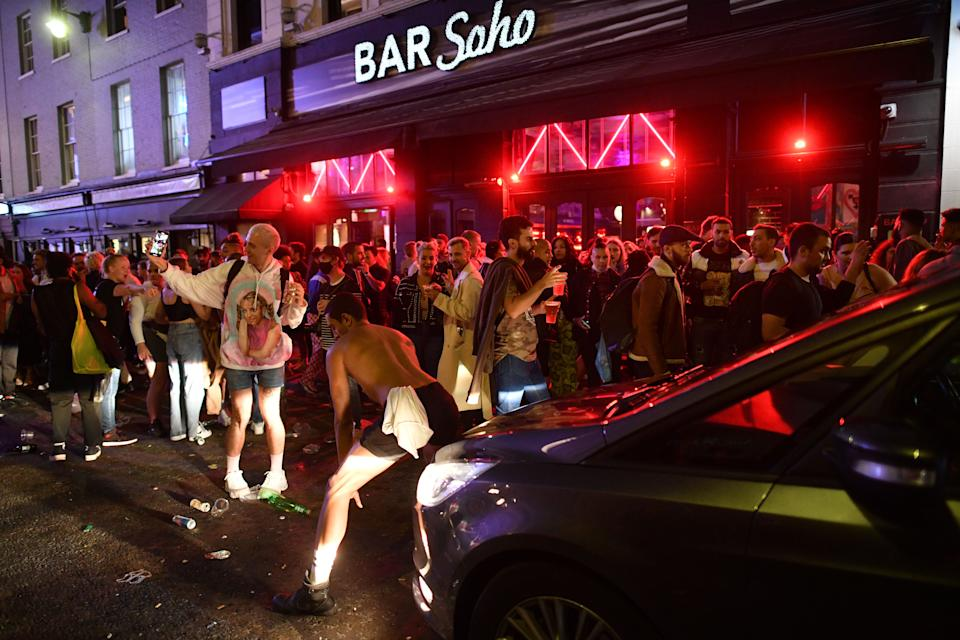 A car tries to drive along a street filled with revellers drinking in the Soho area of London on July 4, 2020, after the police re-opened the road at 2300 as restrictions are further eased during the novel coronavirus COVID-19 pandemic. - Pubs in England reopen on Saturday for the first time since late March, bringing cheer to drinkers and the industry but fears of public disorder and fresh coronavirus cases. (Photo by JUSTIN TALLIS / AFP) (Photo by JUSTIN TALLIS/AFP via Getty Images)