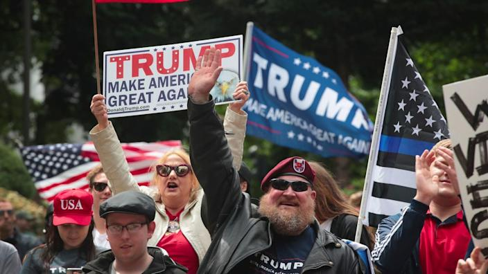 Demonstrators with Trump campaign signs and U.S. flags