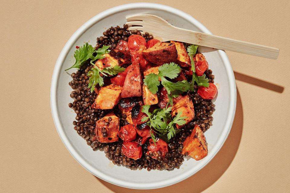 Give sweet potatoes and cherry tomatoes the harissa treatment and spoon them over a bowl of black lentils.