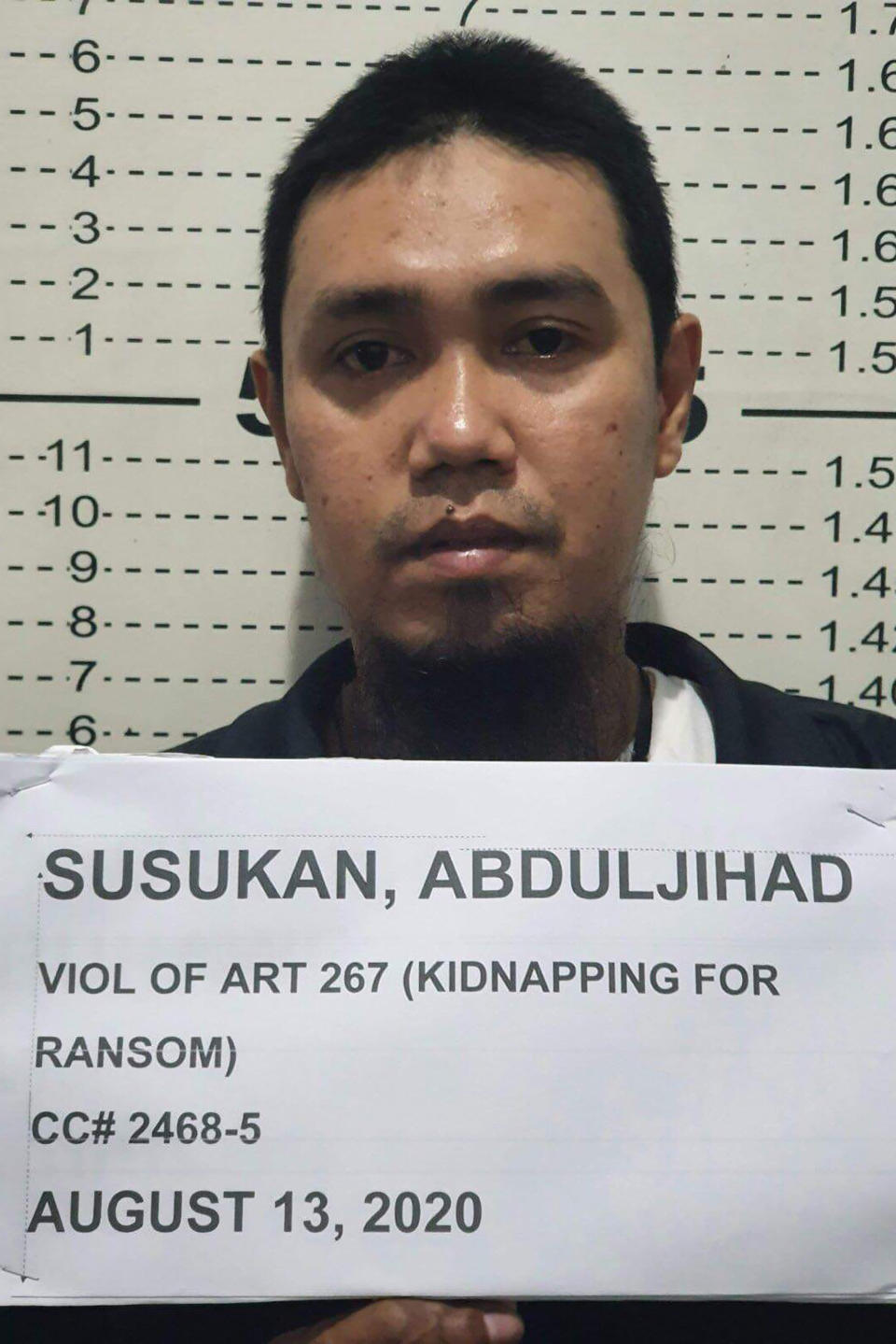 In this photo provided by the Philippine National Police-Public Information Office, Abu Sayyaf commander Anduljihad Susukan poses for a picture at the Davao City Police Station in Davao province, southern Philippines on Thursday Aug. 13, 2020. Susukan, a leading terror suspect who has been linked to beheadings of hostages including two Canadians and a Malaysian, has surrendered after being wounded in battle, officials said Friday. (Philippine National Police PIO via AP)