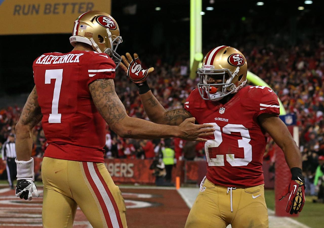 SAN FRANCISCO, CA - JANUARY 12:  Quarterback Colin Kaepernick #7 of the San Francisco 49ers celebrates with running back LaMichael James #23 after running the ball for a touchdown against the Green Bay Packers in the third quarter during the NFC Divisional Playoff Game at Candlestick Park on January 12, 2013 in San Francisco, California.  (Photo by Stephen Dunn/Getty Images)