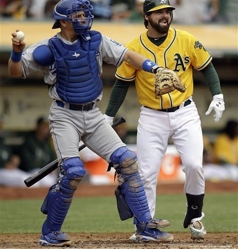 Los Angeles Dodgers catcher Matt Treanor, left, looks to first base after gaining control of a foul tip from Oakland Athletics' Derek Norris, right, during the second inning of a baseball game Thursday, June 21, 2012, in Oakland, Calif. Norris was recalled from Triple-A Sacramento on Thursday in time to start the series finale with the Dodgers. (AP Photo/Ben Margot)