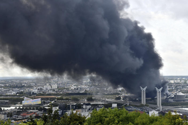 Black smoke is pictured after a fire broke at a chemical plant in Rouen, Normandy, Thursday, Sept.26, 2019. An immense mass of black smoke is rising over Normandy as firefighters battle a blaze at a chemical plant, and authorities closed schools in 11 surrounding towns and asked residents to stay indoors. (AP Photo/Stephanie Peron)