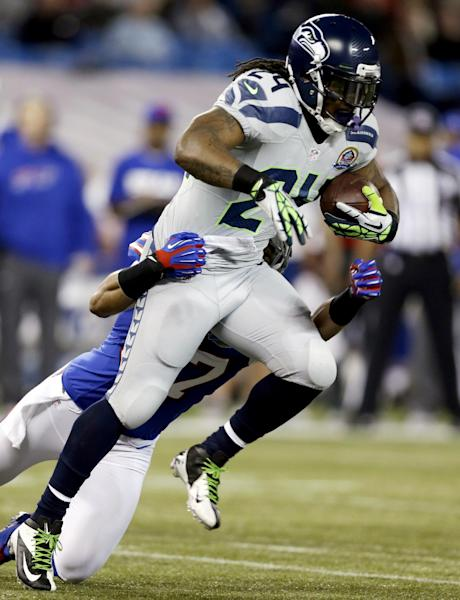 Seattle Seahawks running back Marshawn Lynch (24) is tackled by Buffalo Bills strong safety George Wilson (37) during the first half of an NFL football game, Sunday, Dec. 16, 2012, in Toronto. (AP Photo/Mike Groll)