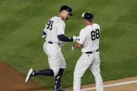 New York Yankees third base coach Phil Nevin (88) congratulates Aaron Judge (99) ater Judge hit a two-run home run in the eighth inning of the team's baseball game against the Boston Red Sox, Sunday, Aug. 2, 2020, at Yankee Stadium in New York. (AP Photo/Kathy Willens)