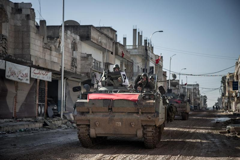 Turkish army vehicles drive in a street of the Syrian town of Kobane on February 22, 2015, during an operation to relieve the garrison guarding the Suleyman Shah mausoleum (AFP Photo/Mursel Coban)