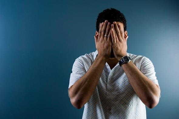 A3DATJ Contemporary image of a man hiding his face indoors  man; hiding; face; anxiety; regrets; alone; shame; men; male; Arabic