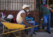 Workers wear masks during the COVID-19 pandemic as they visit on a sidewalk in Havana, Cuba, Tuesday, Oct. 12, 2021. (AP Photo/Ramon Espinosa)