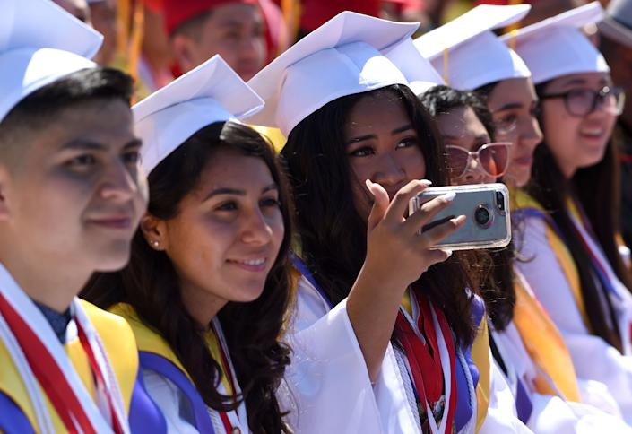 Lakewood High School students singing the alma mater during the graduation ceremony at Veterans Memorial Stadium in Long Beach on Wednesday, June 12, 2019.