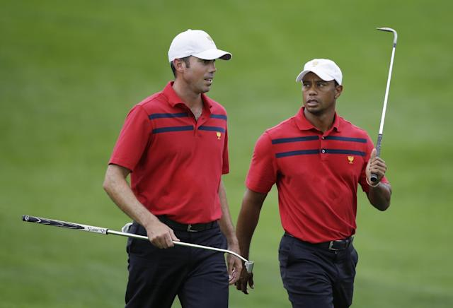 United States' Matt Kuchar, left, talks with Tiger Woods as they walk to the 16th green during a fourball match at the Presidents Cup golf tournament at Muirfield Village Golf Club on Saturday, Oct. 5, 2013, in Dublin, Ohio. Woods and Kuchar defeated International team player Adam Scott, of Australia, and Hideki Matsuyama, of Japan, 1-up. (AP Photo/Darron Cummings)