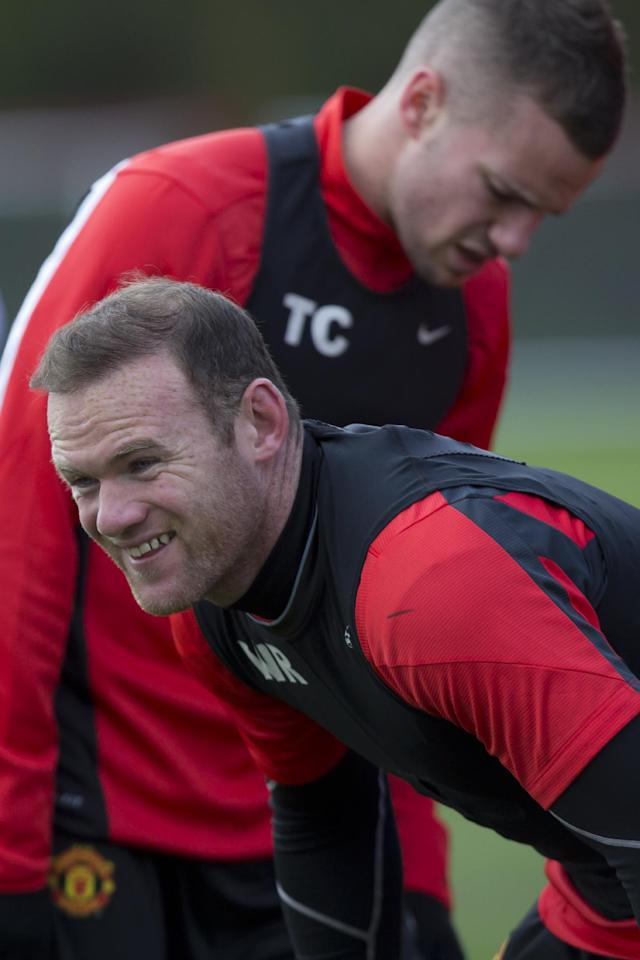 Manchester United's Wayne Rooney, bottom smiles as he trains with teammates at Carrington training ground in Manchester, Tuesday, April 8, 2014. Manchester United will play Bayern Munich in Germany in a Champions League quarter final second leg soccer match on Wednesday. (AP Photo/Jon Super)