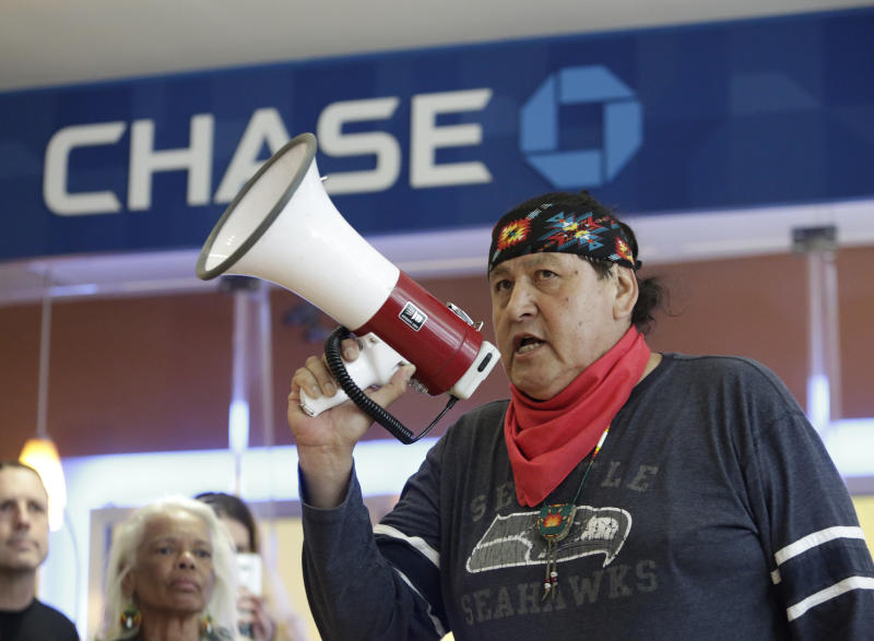 Raymond Kingfisher speaks as indigenous leaders and climate activists disrupt business on May 8 at a Chase Bank branch in Seattle to protest funding tar sands development and projects like the Keystone XL pipeline. (JASON REDMOND via Getty Images)