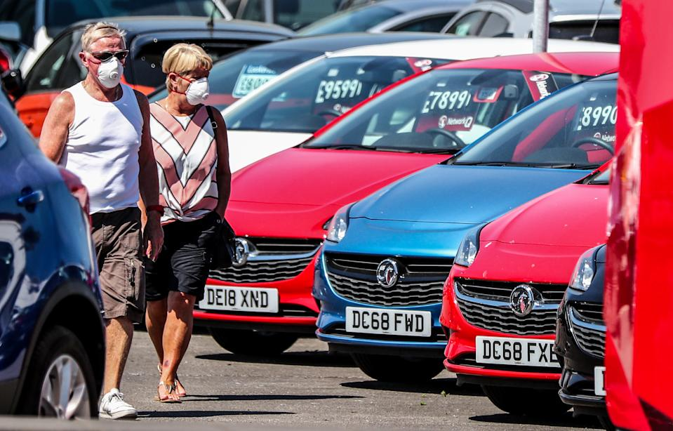 A couple walk past cars on the forecourt of Vauxhall Lookers in Speke, Liverpool, as showrooms open for the first time since lockdown, as part of a wider easing of restrictions in England.
