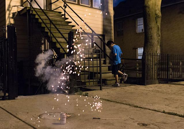 <p>A boy runs away from the firework he set off in a celebration of the Fourth of July in Chicago on Monday, July 3, 2017. Americans are celebrating their country's birthday Tuesday with big-time fireworks, small-town parades and the quirky spectacle of competitive hot dog eating, marking a day of shared traditions in a nation that has grappled with divides this past year. (Photo: G-Jun Yam/AP) </p>