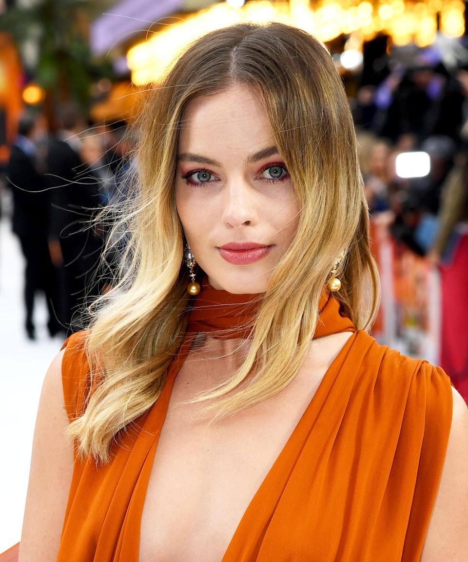 """<h3>Peachy Sunset Tones</h3> <br><br>Robbie proves <a href=""""https://www.refinery29.com/en-us/sunset-makeup-trend"""" rel=""""nofollow noopener"""" target=""""_blank"""" data-ylk=""""slk:sunset eyeshadow"""" class=""""link rapid-noclick-resp"""">sunset eyeshadow </a>is the way to style a smoky eye in the summer. At the UK premiere of <em>Once Upon A Time...in Hollywood</em>, Dubroff gave the actress an unexpectedly piercing peach-gold shadow moment to match her gathered-silk Oscar De La Renta gown.<span class=""""copyright"""">Photo: Dave J Hogan/Getty Images.</span><br><br>"""