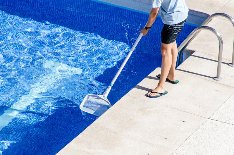 A man standing at the edge of a pool, skimming the surface with a cleaning net.