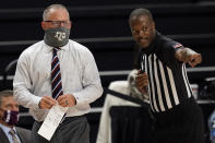 Texas A&M head coach Buzz Williams, left, talks to a game official during the first half of an NCAA college basketball game against New Orleans on Sunday, Nov. 29, 2020, in College Station, Texas. (AP Photo/Sam Craft)