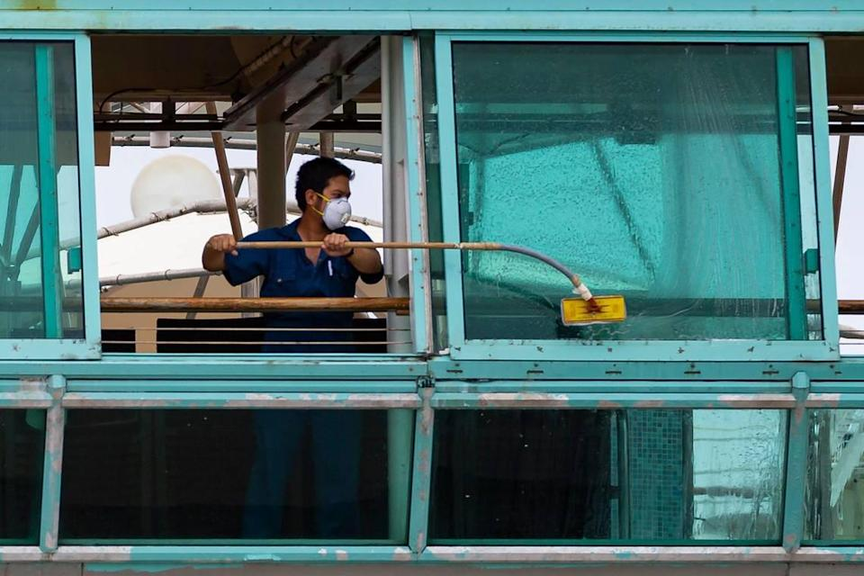 A crew member aboard Royal Caribbean's Vision of the Seas cruise ship cleans the window as the ship is docked at PortMiami on Friday, May 15, 2020, in Miami, Florida.