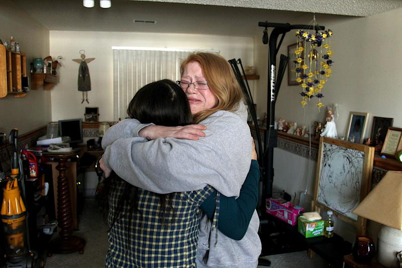 Family friend of Melissa Aryal, Sara Johnson, comforts Savannah Laventure, 18, the sister of shooting victim 9-year-old Devin Aryal, at the Aryal family home, Tuesday, Feb. 12, 2013 in Oakdale, Minn. (AP Photo/The Star Tribune, Elizabeth Flores)