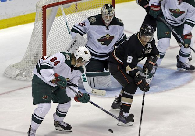 Anaheim Ducks right winger Teemu Selanne (8), of Finland, maneuvers the puck with Minnesota Wild center Mikael Granlund (64), of Finland, and goalie Darcy Kuemper (35) defending in the second period of an NHL hockey game in Anaheim, Calif., Tuesday, Jan. 28, 2014. (AP Photo/Reed Saxon)