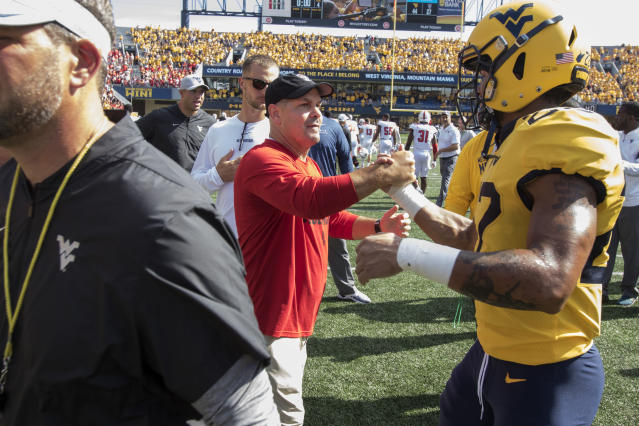 North Carolina State co-defensive coordinator Tony Gibson shakes hands with West Virginia cornerback Hakeem Bailey (24) at the conclusion of an NCAA college football game Saturday, Sept. 14, 2019, in Morgantown, W.Va. Last year Gibson served as defense coordinator for West Virginia. (AP Photo/Raymond Thompson)