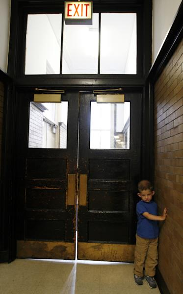 Luka Riner, 4, clings to a wall at Trumbull Elementary School on the last day of school, Monday, June 24, 2013 in Chicago. Trumbull is one of several Chicago public schools that closed this month in an effort to save money and consolidate resources. Luka, who was born is developmentally delayed and diagnosed at birth with a condition called Trisomy 9 Syndrome, was a student in the school's preschool program, where he also received special education services, including physical, speech and occupational therapy. Luka will be moving to a new public preschool in the fall, though his mom isn't happy with the one he's been assigned to. She's currently trying to get him into one closer to their home. (AP Photo/Martha Irvine)