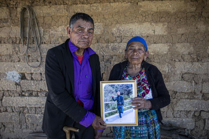 German and Maria Tomas pose for a photograph holding a framed portrait of their grandson Ivan Gudiel, at their home in Comitancillo, Guatemala, Wednesday, Jan. 27, 2021. They believe their grandson is one of the 13 of the 19 charred corpses found in a northern Mexico border state on Saturday. The country's Foreign Ministry said it was collecting DNA samples from a dozen relatives to see if there was a match with any of the bodies. (AP Photo/Oliver de Ros)