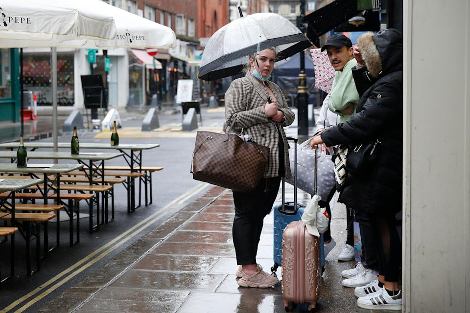 <p>People stand outside in the rain near temporary outdoor seating in Soho</p> (Getty Images)