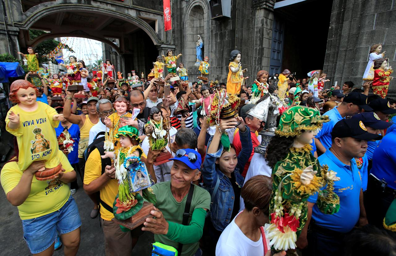 Devotees parade different figurines of Santo Nino (infant Jesus) during a procession in Tondo city, Metro Manila, Philippines January 20, 2018, a day before the annual of the feast day of Santo Nino on Sunday. REUTERS/Romeo Ranoco