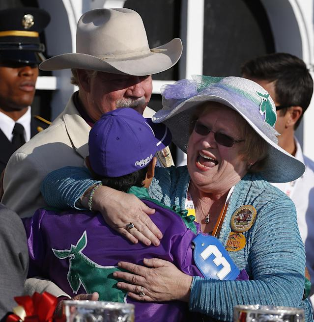 Jockey Victor Espinoza, left, embraces Carolyn Coburn as co-owner Steve Coburn looks on as they celebrated in the winner's circle after California Chrome won the 139th Preakness Stakes horse race at Pimlico Race Course, Saturday, May 17, 2014, in Baltimore. (AP Photo/Matt Slocum)