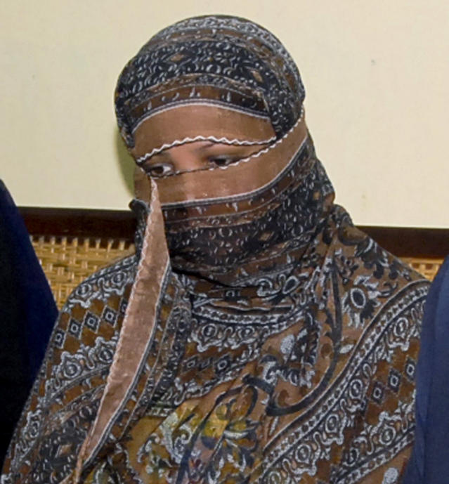 FILE - In this Nov. 20, 2010, file photo, Aasia Bibi, a Pakistani Christian woman, listens to officials at a prison in Sheikhupura near Lahore, Pakistan. In Mid January 2019, the Pakistani Christian woman still lives the life of a prisoner, although she was freed from death row by the country's top court more than two months ago. Meanwhile, a petition by Islamist radicals who rallied against her acquittal of blasphemy charges and who seek her execution awaits a Supreme Court decision. (AP Photo, File)