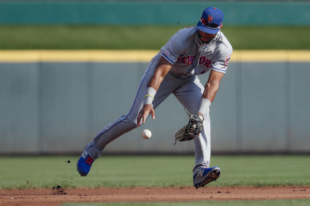 New York Mets shortstop Amed Rosario bobbles the ball after third baseman Todd Frazier commited an error on a fielder's choice hit by Cincinnati Reds' Eugenio Suarez off starting pitcher Zack Wheeler in the first inning of a baseball game, Saturday, Sept. 21, 2019, in Cincinnati. (AP Photo/John Minchillo)
