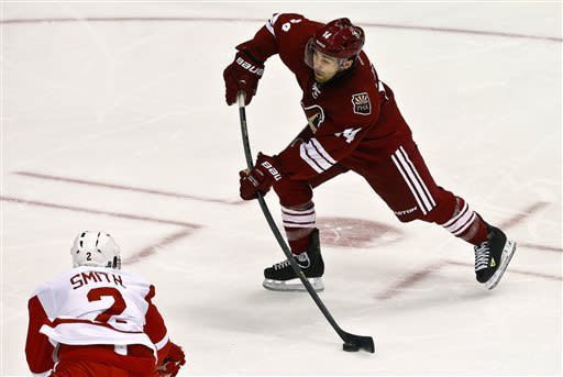 Phoenix Coyotes' Chris Conner (14) sends a shot past Detroit Red Wings' Brendan Smith (2) and past the Red Wings goalie for a score in the second period during an NHL hockey game on Thursday, April 4, 2013, in Glendale, Ariz. (AP Photo/Ross D. Franklin)