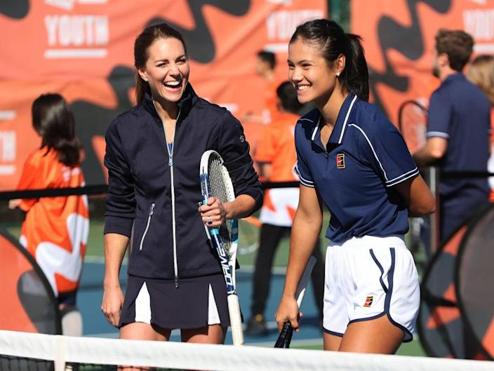 Kate Middleton laughs as she plays tennis with Emma Raducanu (R) (Getty Images for LTA)