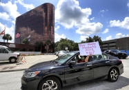 FILE - In this July 7, 2020, file photo, a teacher holds up a sign while driving by the Orange County Public Schools headquarters as educators protest in a car parade around the administration center in downtown Orlando, Fla. As the Trump administration pushes full steam ahead to force schools to resume in-person education, public health experts warn that a one-size-fits-all reopening could drive infection and death rates even higher. (Joe Burbank/Orlando Sentinel via AP, File)