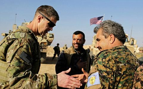 A US military adviser shakes hands with a Kurdish commander in Manbij in northern Syria last week - Credit: Susannah George/AP Photo