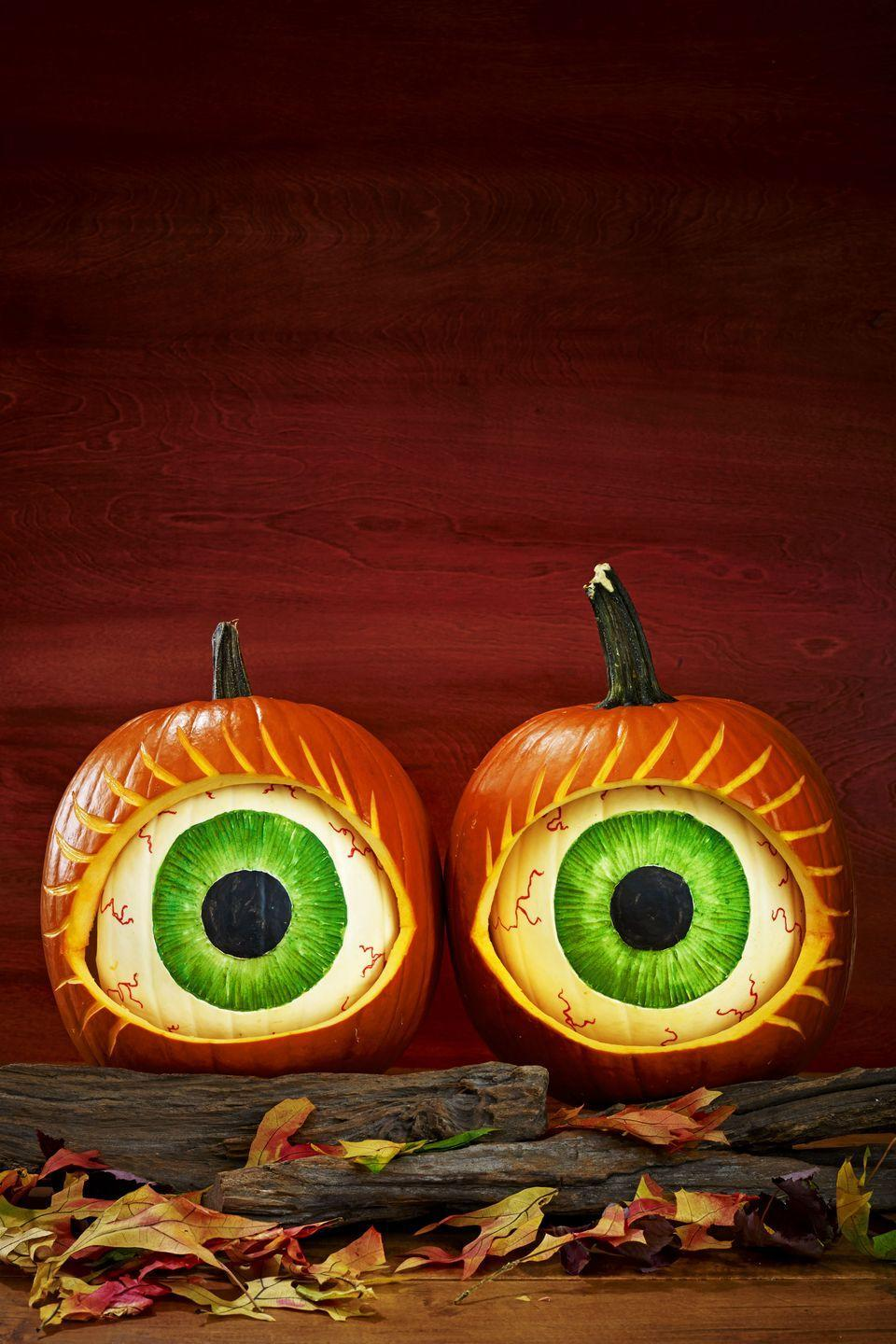 """<p>Keep an eye (or two) on the neighborhood with these creepy carved pumpkins. The secret? A smaller white pumpkin goes <em>inside </em>a larger orange pumpkin.</p><p><a href=""""https://www.womansday.com/home/crafts-projects/a28713862/eye-see-you-pumpkins/"""" rel=""""nofollow noopener"""" target=""""_blank"""" data-ylk=""""slk:Get the Pumpkin Eyes tutorial."""" class=""""link rapid-noclick-resp""""><strong><em>Get the Pumpkin Eyes tutorial.</em></strong></a></p>"""