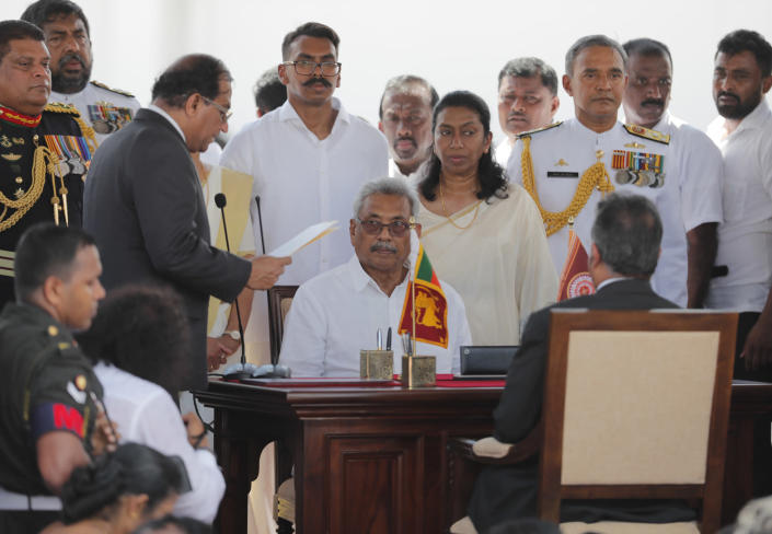 Sri Lanka's newly elected president Gotabaya Rajapaksa, center seated, looks on as secretary to the president Udaya Seneviratne, left, reads a document during the swearing in ceremony held at the 140 B.C Ruwanweli Seya Buddhist temple in ancient kingdom of Anuradhapura in northcentral Sri Lanka Monday, Nov. 18, 2019. The former defense official credited with ending a long civil war was Monday sworn in as Sri Lanka's seventh president after comfortably winning last Saturday's presidential election. (AP Photo/Eranga Jayawardena)