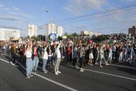 "People with flowers and old Belarusian national flags shout slogan ""Go away!"" as they gather to protest against the results of the country's presidential election in Minsk, Belarus, Thursday, Aug. 13, 2020. Crowds of protesters in Belarus swarmed the streets and thousands of workers rallied outside industrial plants to denounce a police crackdown on demonstrations over a disputed election that extended the 26-year rule of authoritarian President Alexander Lukashenko. (AP Photo/Sergei Grits)"