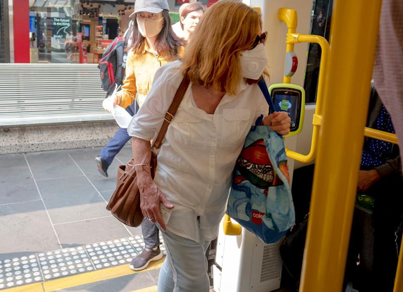 Melbourne commuters board a tram wearing masks. Source: Getty