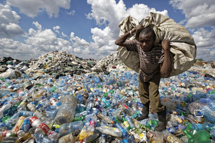 FILE - In this Wednesday, Dec. 5, 2018 file photo, a man walks on a mountain of plastic bottles as he carries a sack of them to be sold for recycling after weighing them at the dump in the Dandora slum of Nairobi, Kenya. The oil industry in 2020 has asked the United States to pressure Kenya to change its world-leading stance against the plastic waste that litters Africa, according to environmentalists who fear the continent will be used as a dumping ground. (AP Photo/Ben Curtis, File)