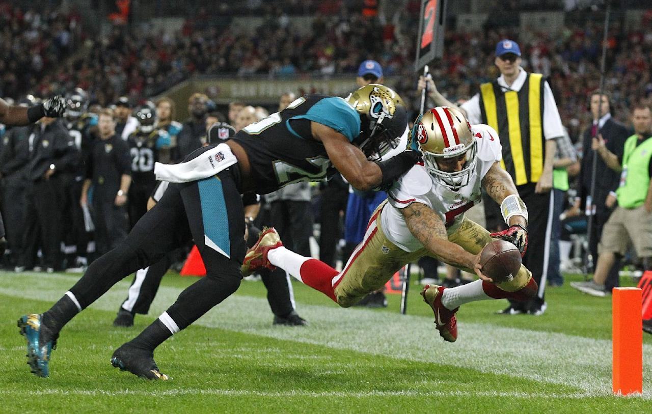 San Francisco 49ers quarterback Colin Kaepernick (7), right, dives to score a touchdown despite the challenge of Jacksonville Jaguars free safety Josh Evans (26) during the NFL football game between San Francisco 49ers and Jacksonville Jaguars at Wembley Stadium in London, Sunday, Oct. 27, 2013. (AP Photo/Sang Tan)