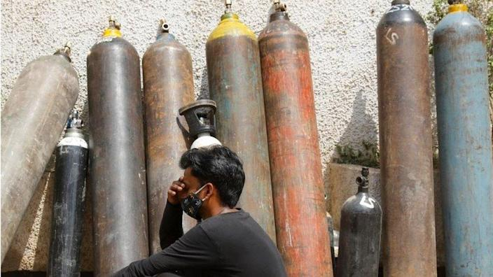 A man waits outside a factory to get his oxygen cylinder refilled, amidst the spread of the coronavirus disease (COVID-19) in New Delhi, India, April 28, 2021. REUTERS/Adnan Abidi