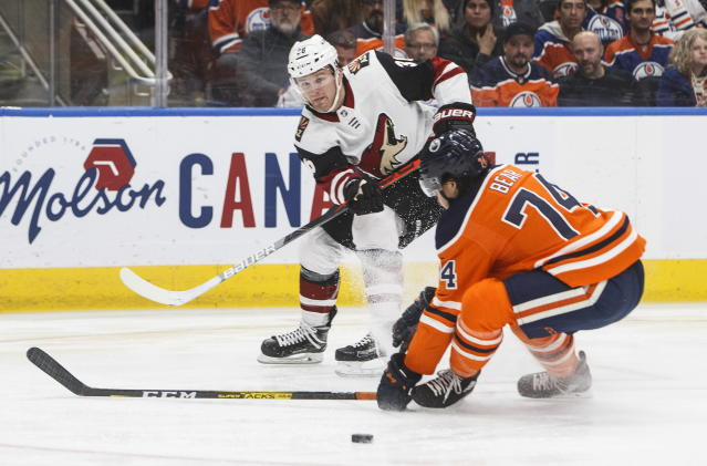Arizona Coyotes ' Christian Fischer (36) shoots as Edmonton Oilers' Ethan Bear (74) tries to block during first-period NHL hockey game action in Edmonton, Alberta, Monday, Nov. 4, 2019. (Jason Franson/The Canadian Press via AP)
